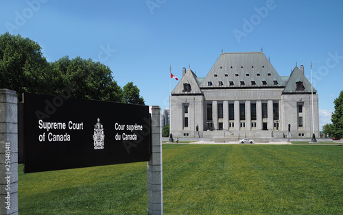 The Supreme Court of Canada with its sign on a long lawn.
