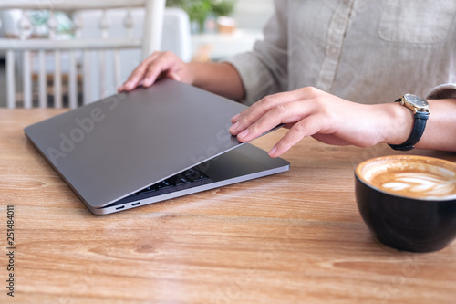 Foto Closeup image of a woman close and open a laptop computer on table after finishe