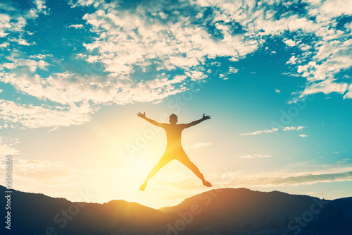 Fotografia  Happy man jumping at top of mountain with sunset sky abstract background