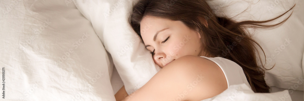 Fototapeta Above panoramic view young woman sleeping in bed hugging pillow