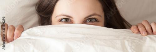 Photo  Horizontal image woman hiding under white blanket lying on pillow