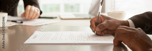 Horizontal closeup image black businessman sitting at desk signing contract Canvas-taulu