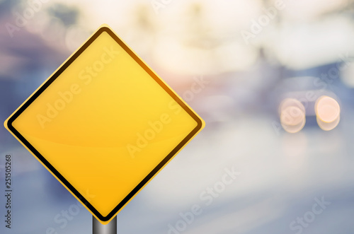 Fotografía Empty yellow traffic sign on blur traffic road with colorful bokeh light abstract background