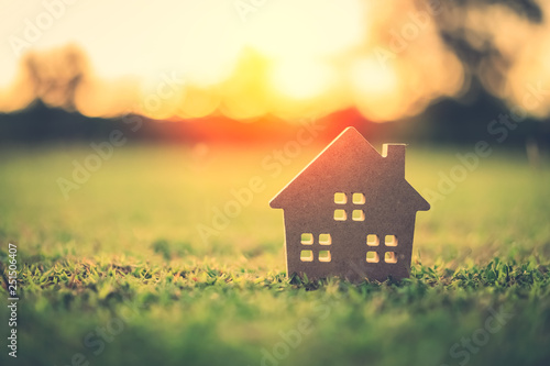 Copy space of home and life concept. Small model home on green grass with sunlight abstract background.