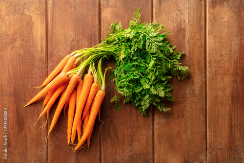 Fotografía  An overhead photo of fresh organic raw carrots on a dark rustic wooden backgroun