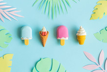 Ice Cream On Stick And In Wafer Cone With Multicolored Origami Tropical Leaves Abstract On Blue.