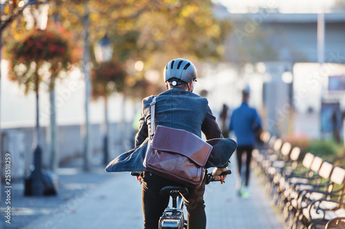 A rear view of businessman commuter with electric bicycle traveling to work in city Canvas