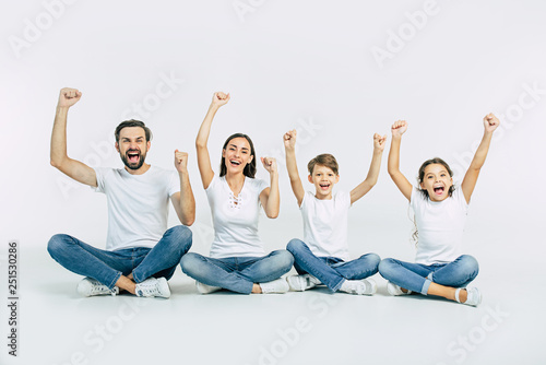 Obraz Happy and cheerful young beautiful family are smiling and posing while have a fun together over white background - fototapety do salonu
