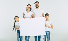 Beautiful Smiling Family In White T-shirts Hold In Hands The Big Blank Banner And Looking On Camera