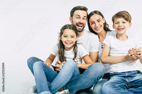 Fototapeta Relationship concept. Beautiful and happy smiling young family in white T-shirts are hugging and have a fun time together while sitting on the floor and looking on camera. obraz