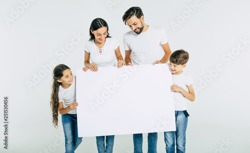 Fotografía  Beautiful smiling family in white T-shirts hold in hands the big blank banner an
