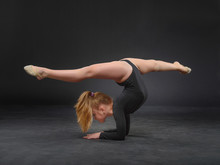 Beautiful White Caucasian Girl Gymnast Doing Gymnastic Exercise For Flexibility And Stretching On Black Background.