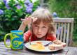 Cute little boy with blonde hair having breakfast in the garden