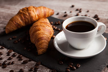 Two Fresh Croissants And Cup Of Coffee On Dark Stone Table