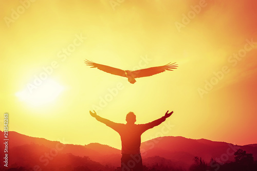 Tuinposter Ontspanning Man raise hand up on top of mountain and sunset sky with eagle bird fly abstract background.