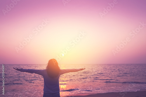 Photo Stands Candy pink Copy space of woman rise hand up on sunset sky at beach and island background.