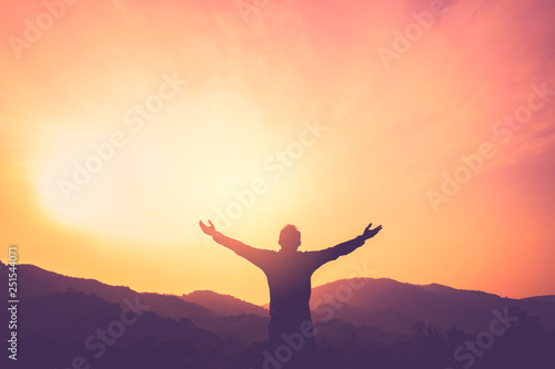 Photo  Copy space of man rise hand up on top of mountain and sunset sky abstract background