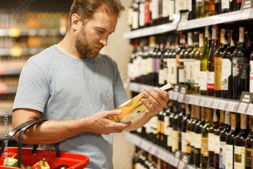 Fotografía  Bearded man holding bottle of white wine and choosing beverages