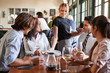 canvas print picture - Waitress Serving Meal To Business Colleagues Sitting Around Restaurant Table