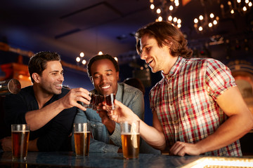 Group Of Male Friends Drinking Shots In Bar Together