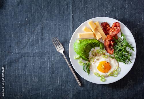 Fototapeta healthy keto breakfast: egg, avocado, cheese, bacon obraz