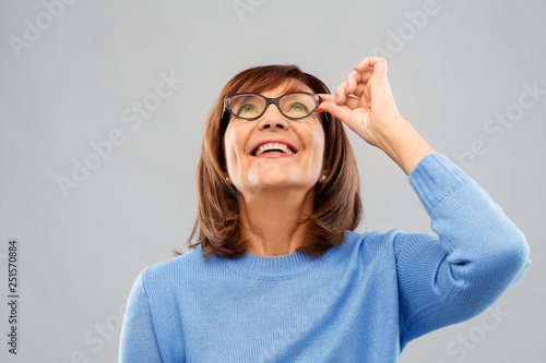 vision and old people concept - portrait of smiling senior woman in glasses looking up over grey background