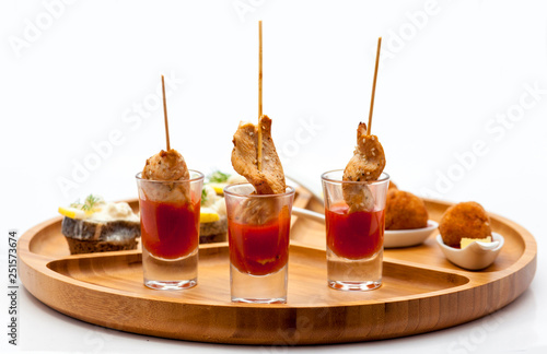 Slika na platnu Assortment of snacks and appetizers on wooden plate
