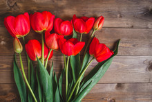 Row Of Red Tulips On Wooden Ba...