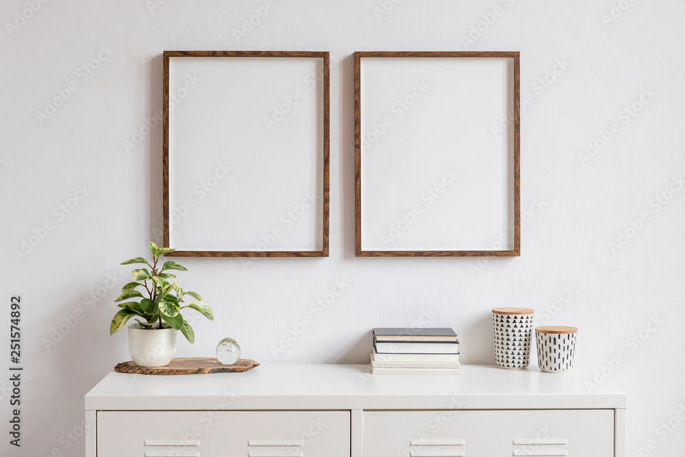 Fototapety, obrazy: Minimalistic home decor of interior with two brown wooden mock up photo frames on the white shelf with books, beautiful plant in stylish pot and home accessories. White wall.