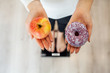 Diet. Woman Measuring Body Weight On Weighing Scale Holding Donut and apple. Sweets Are Unhealthy Junk Food. Dieting, Healthy Eating, Lifestyle. Weight Loss. Obesity. Top View