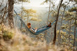 canvas print picture - Young happy man relaxing lying in hammock on top of mountain.