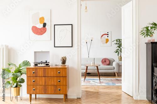 Stylish retro living room with design grey sofa, retro table ...