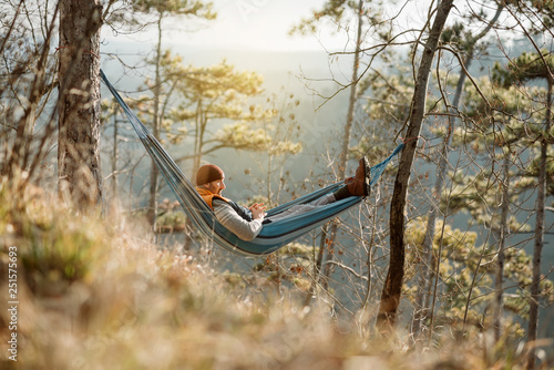 Fotomural  Young happy man relaxing lying in hammock on top of mountain.