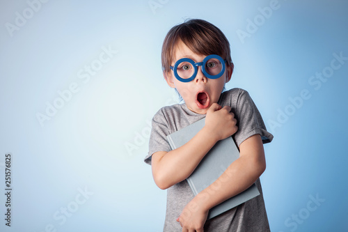 Fotografía  Portrait of a beautiful cute baby boy in blue glasses on a blue background