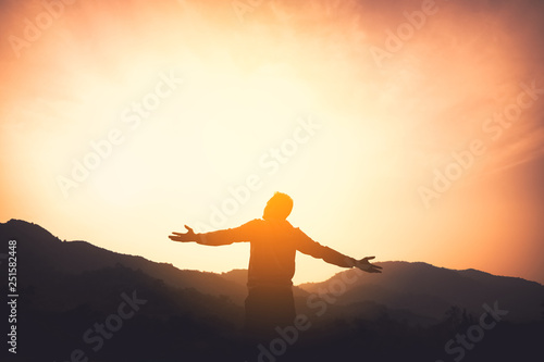 Fotomural Copy space of man rise hand up on top of mountain and sunset sky abstract background