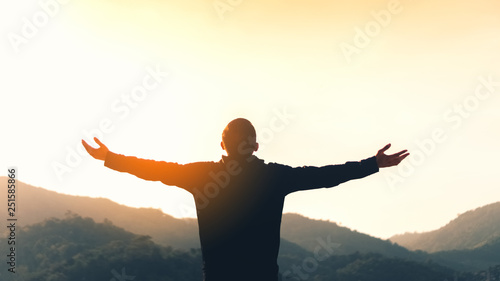 Foto  Copy space of man rise hand up on top of mountain and sunset sky abstract background