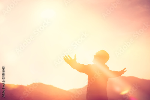 Leinwand Poster Copy space of man rise hand up on top of mountain and sunset sky abstract background