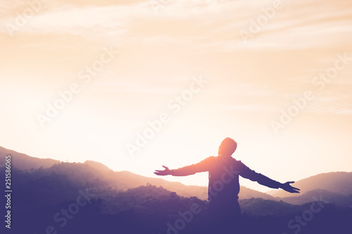 Obraz na plátně Copy space of man rise hand up on top of mountain and sunset sky abstract background
