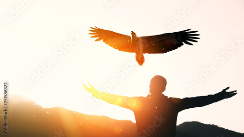 Acrylic Prints Eagle Man raise hand up on top of mountain and sunset sky with eagle bird fly abstract background.
