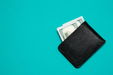 Black Leather Wallet With Dollar Bills On Blue Background. Men's Purse With Money Bills
