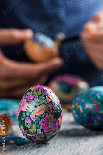 young man decorating homemade easter eggs.