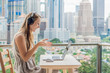 canvas print picture - Young woman teaches a foreign language or learns a foreign language on the Internet on her balcony against the backdrop of a big city. Online language school lifestyle