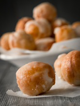 Small Homemade Doughnuts, Also Known As Doughnut Holes, Prepared For Polish Fat Thursday. On The Foreground Three Doughnuts On A Piece Of Baking Paper, In The Background A White Bowl Full Of Doughnuts
