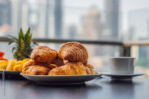 Breakfast table with coffee fruit and bread croisant on a balcony against the ba Canvas Print