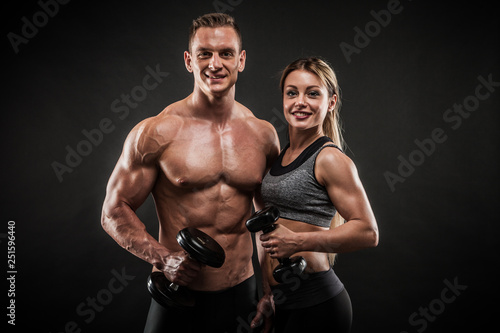 Fotografiet  Sporty young couple posing on black background