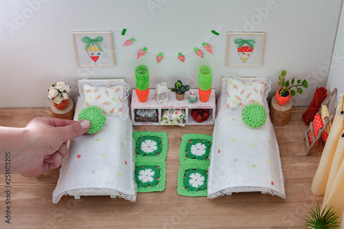 Photo Hand decorating a dollhouse bedroom, Doll wooden furniture in a children play ro