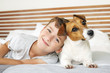 Happy boy playing with his dog, Jack Russell Terrier, waking up early in the morning, in a bed in white bedding. Smiling child and his pet basking in bed. Resort vacation at the hotel