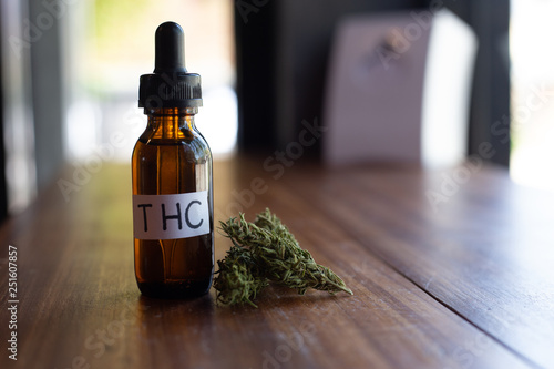Fotografia  Medicinal cannabis with extract oil in a bottle.