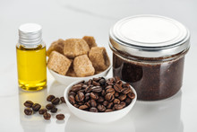 Selective Focus Of Bowls With Brown Sugar Cubes And Coffee Grains, And Glass Containers With Ground Coffee Scrub And Oil On White Surface