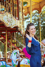 Smiling Elegant Tourist Woman Riding On Carousel And Waving